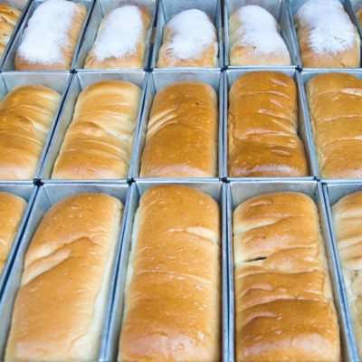 Pan lubrication is a critical step in high-speed bakeries processing thousands of loaves per hour.