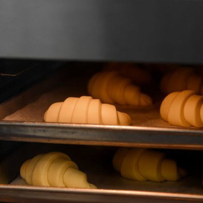 A convection oven uses fans to circulate hot air around the product placed on racks in the baking chamber, good for products like pastry.