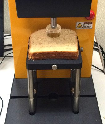 A slice of bread being tested on a texture analyzer.